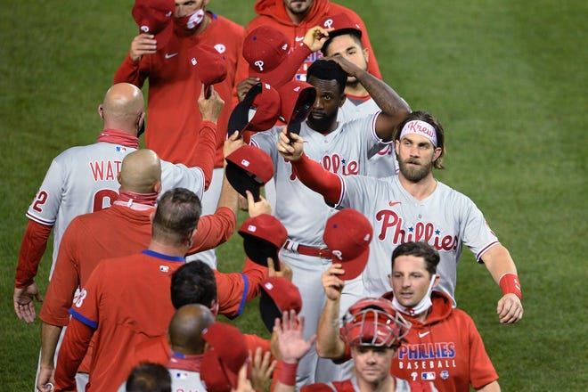 The Phillies, including Bryce Harper (with headband), celebrate Wednesday night's 12-3 win over the Nationals.