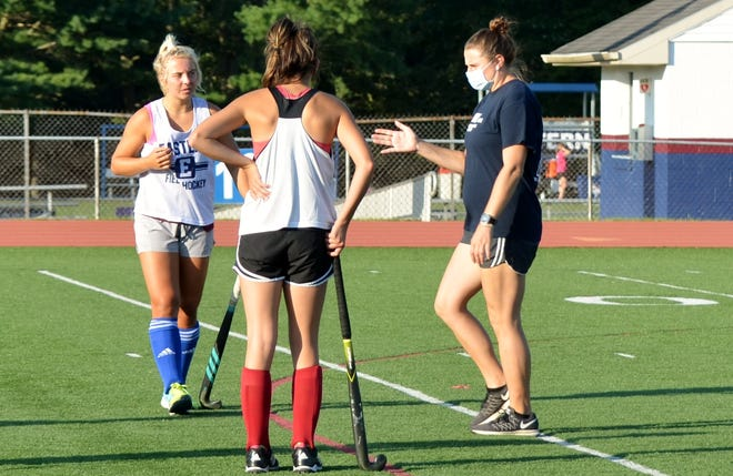 Eastern field hockey first-year coach Alexandra Marshall, right, explains a point during a preseason practice.