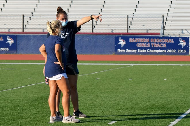 Eastern field hockey assistant coach Kerry Heck, left, listens as first-year head coach Alexandra Marshall makes a point
