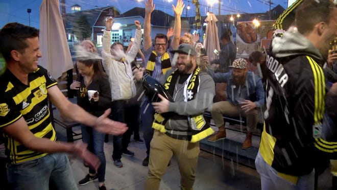 With lots of champagne, more than a 1,000 Crew soccer fans celebrate at Endeavor Brewing Company on Oct. 12, 2018 after MLS announced it was in advanced discussions with the Haslam and Edwards families on buying the Crew. (Doral Chenoweth III/Dispatch)