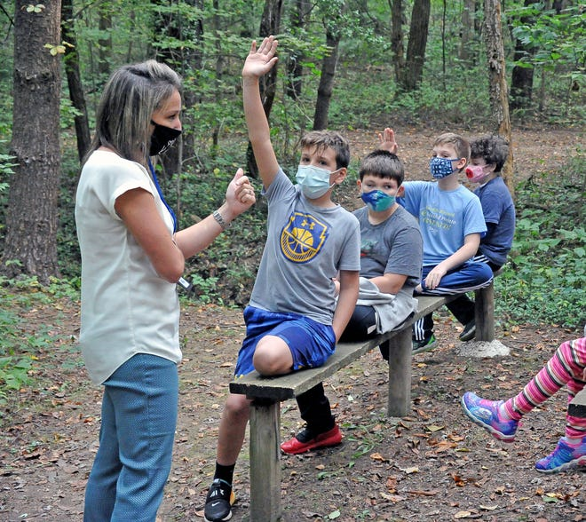 Jamie Zollinger, Chippewa Intermediate School principal, talks with fourth-grade students before they enter the Parfit's Paradise area on Thursday to look for traces of local animals, which they can use when making comparisons to fossils.