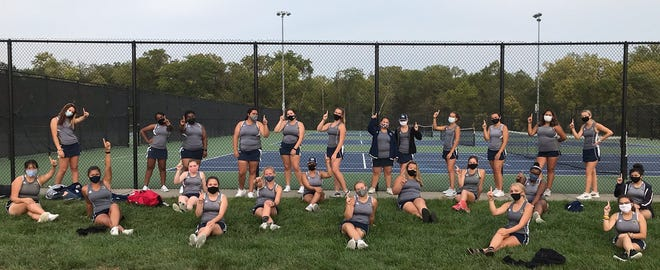 The William Chrisman girls tennis players signal No. 1 after defeating Belton 9-0 Tuesday to clinch at least a share of their third straight conference title.