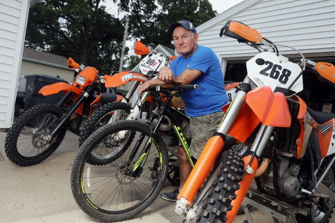 "Bob Schnathorst sits on his Trek mountain bike between a pair of KTM motorcycles Wednesday at his Burlington home. Schnathorst has been off-road motorcycling for the last 50 years. He is a member of the local club, ""Valley Dusters,"" and many weekends he can be found at one of their gatherings or traveling throughout the Midwest to the many events in the trail runner's world."