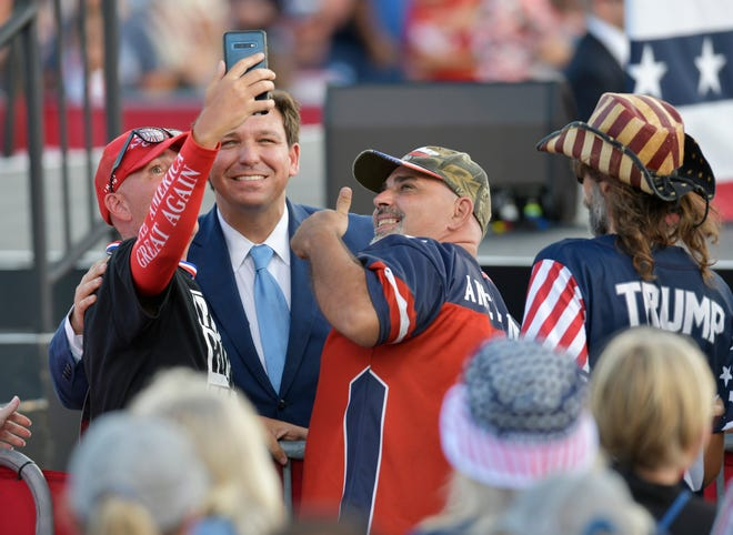 Gov. Ron DeSantis poses for pictures as the crowd waits for President Donald Trump to arrive at Cecil Commerce Center last Thursday.