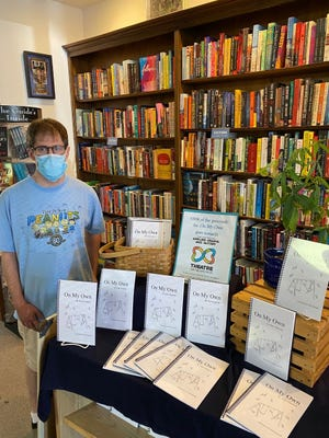 Sean Giannetti of Hudson stands near the display created at The Learned Owl for his book of poems.