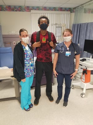 Christian Walker, in center, at All Children's Specialty Clinic in Tampa where he's been receiving transfusions to help control his blood disorder. With him are nurses Darlene Glye and Jamie Hornyak.