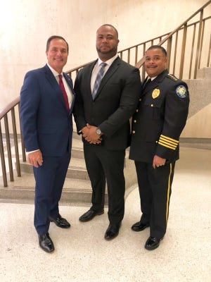 Patrick Adolphe of Delray Beach (center) stands with State Rep. Mike Caruso and Delray Beach Police Chief Javaro Sims on Wednesday at the state capital in Tallahassee. Adolphe was granted a full pardon on a 2009 felony theft conviction. He was later offered a position with the Delray Beach Police Department. [Photo provided]