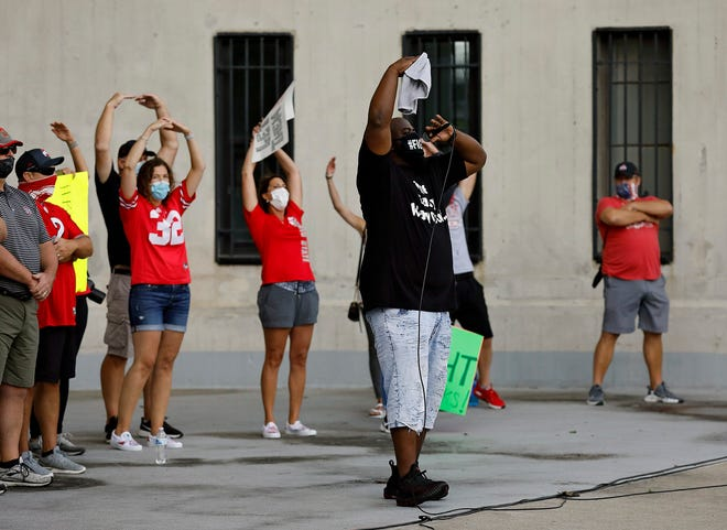 Randy Wade, father of Ohio State player Shaun Wade, helps spell out the O-H-I-O chant during a late August rally organized by parents of the Buckeyes football team to protest the Big Ten's decision to not play football this fall. A month later, the conference is preparing to start playing amid the coronavirus pandemic.