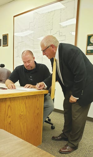 Pratt Police Chief Nate Humble and Pratt city commissioner Doug Meyer look over a grant award  that wil be used by the police department to support drug enforcement activities.
