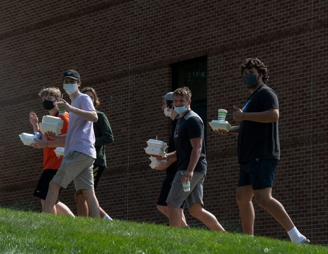 Masked Kent State students walk with their food carry-out orders. The university recently began exclusively offering to-go dining, and implemented heightened COVID-19 related protocols due to increased positive cases within the university community.