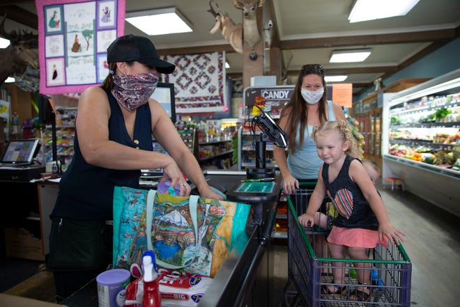 Coco Davis smiles behind her mask at Cassie Mortimore she bags groceries for Carolyn Mortimore at the Fossil Mercantile in Fossil, Oregon, Sept. 4, 2020.