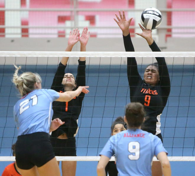 Trinity Lamp (1) and Amirah Mitchell (9) of Massillon defends as Reese Grisez (21) of Alliance goes for a kill during Wednesday's match.