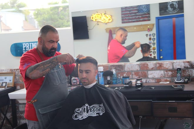 Primo's barbershop owner Juan Desmarais gives a haircut to Josue Baez of Yreka on Tuesday.