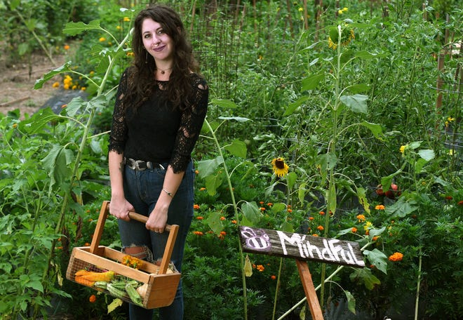 Jordyn Appel-Hughes, the Local Motive Program Director with Feast Down East, stands in front of her garden at her home in Atkinson, N.C., Friday, August 14, 2020. A significant portion of what is grown in the garden is used by the non-profit. Appel-Hughes is one of the 40 Under 40 honorees for 2020.