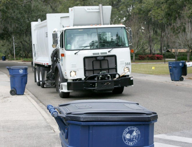 A Panama City garbage truck picks up trash along Bonita Avenue.