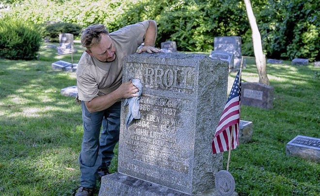 Mike Serrott, a member of the city parks and recreation staff, cleans the gravestone of U.S. soldier and Delaware resident John Carroll, who died in France from the Spanish flu after World War I. Carroll was reinterred at Delaware's Oak Grove Cemetery on Sept. 26, 1920.