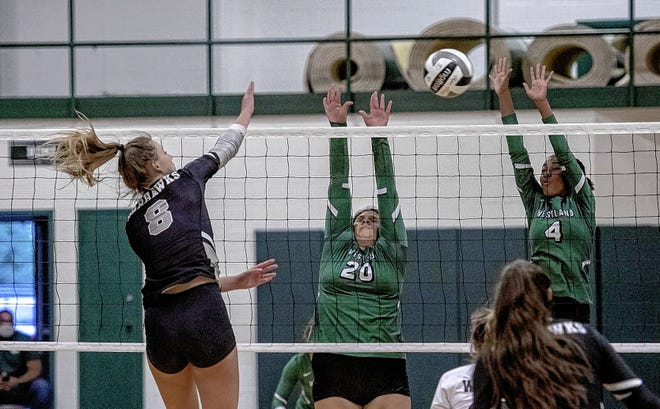 Lyhea Correa (20) and Olivia Fernandez of the Westland girls volleyball team go up for a block against Westerville Central's Riley Kindall during a 25-9, 25-12, 25-4 loss to the visiting Warhawks on Sept. 22. The Cougars were 3-9 overall and 0-4 in the OCC-Ohio before playing Grove City on Sept. 24.