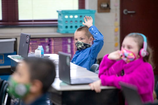 """Third-grader Benjamin Beddingfield raises his hand as he attends class at Upward Elementary School on Sept. 24, 2020. Henderson County Schools students returned to their physical school buildings under """"Return to Learn Plan B"""" this week."""