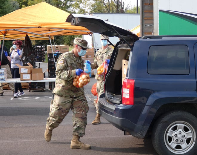 Ohio National Guard soldiers and workers from Second Harvest of North Central Ohio fill empty trunks with an assortment of fresh food during a drive-thru food pantry outside Galion Middle School on Wednesday afternoon.