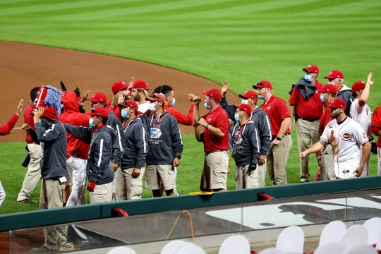 The Cincinnati Reds high fives the grounds crew at the conclusion of the 6-1 win against the Milwaukee Brewers, Wednesday, Sept. 23, 2020, at Great American Ball Park in Cincinnati. The Cincinnati Reds won 6-1.