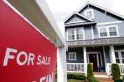 """In this April 1, 2020 photo, a """"For Sale"""" sign stands in front of a home that is in the process of being sold in Monroe, Wash., outside of Seattle."""
