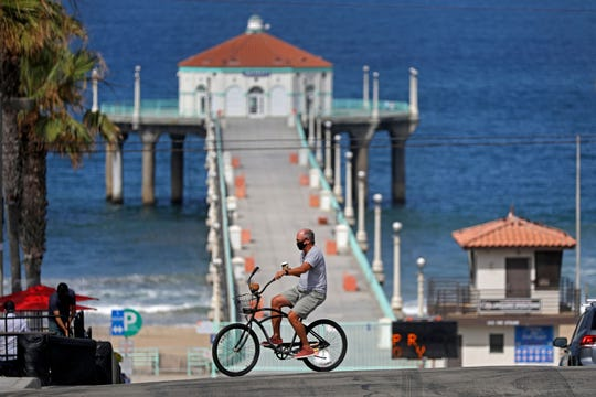 A bicyclist rides along Highland Avenue, with the pier closed to beachgoers, on July 3, 2020, in Manhattan Beach, California.