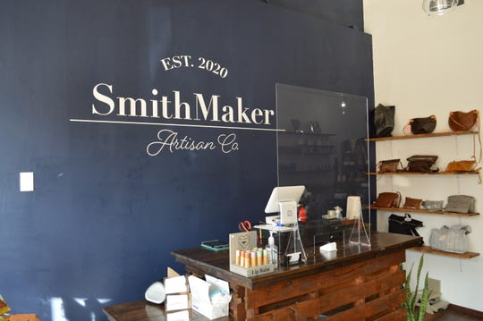 SmithMaker Artisan Co. installs Plexiglas at the register.