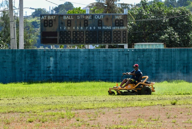 A worker uses a riding mower to regain control of the grass growing within the playing field of the Paseo Stadium in Hagåtña on Thursday, Sept. 24, 2020. Tye Department of Parks and Recreation has just four employees maintainingmore than 74 parks and beaches.