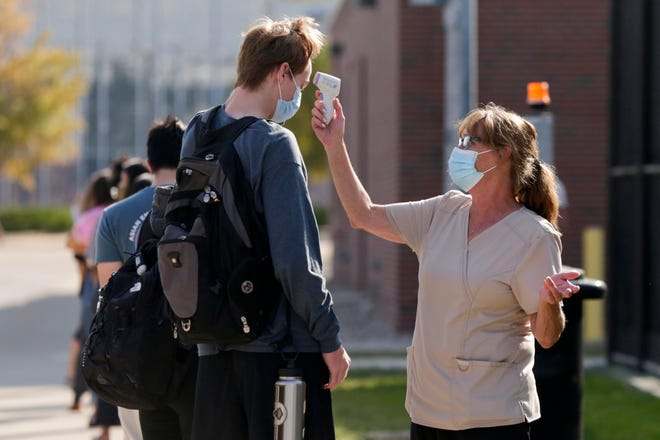 A nurse take a student's temperatures as they queue outside Purdue University's Turf Recreation and Exercise Center for COVID-19 testing, Thursday, Sept. 24, 2020 in West Lafayette.