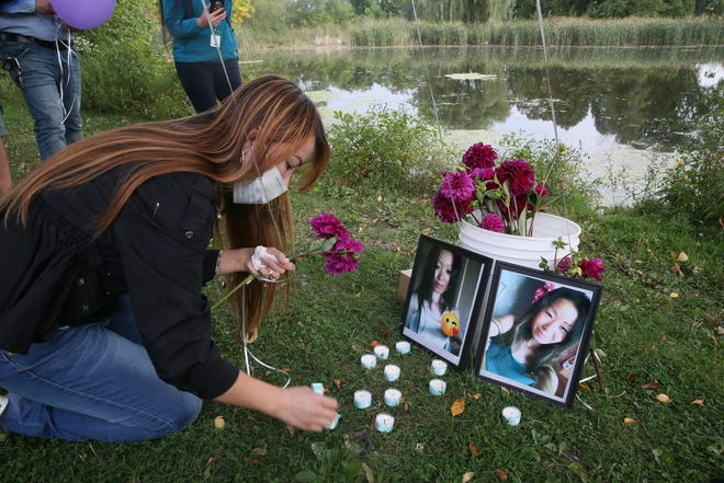 Nancy Lee, the older sister of  Ee Lee, lights candles next to photographs of her sister at Washington Park Lagoon at 1859 N. 40th St. in Milwaukee on Thursday, Sept. 24, 2020, during a candlelight vigil. A crowd of about 50 wrote messages on balloons and lit candles to honor her memory.