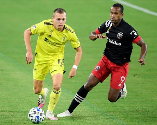 Nashville SC defender Alistar Johnston (12) advances past D.C. United forward Ola Kamara (9) during the first half at Nissan Stadium in Nashville, Tenn., Wednesday, Sept. 23, 2020.
