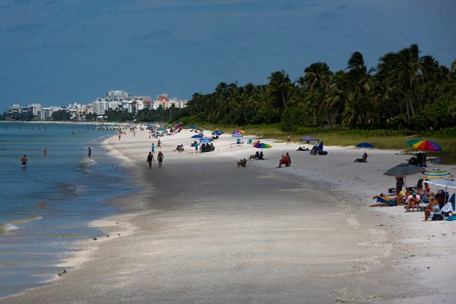 Visitors relax along along the shore of Naples beach, Wednesday, Sept. 23, 2020.