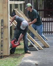 Chase Arnette and Dalton McGhee of Southern Services work to rebuild a fence damaged by Hurricane Sally in the Cordova Park area on Thursday, 24, 2020.