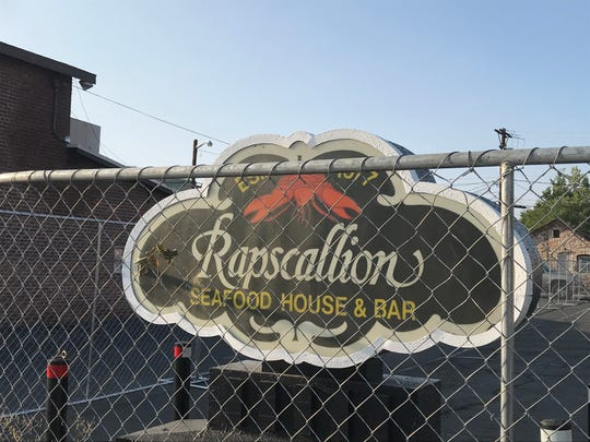 The Rapscallion sign appears from behind the chain link fence erected around the restaurant on Sept. 21, 2020. The restaurant has been closed since the coronavirus shutdown began.