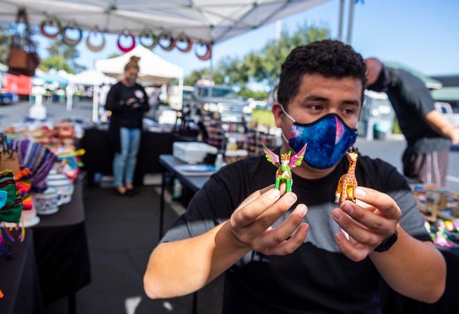 Victor Rios, 19, holds two alebrijes during a farmers market in San Jose, Calif., on Wednesday, Sept. 23, 2020. Rios works part time at his mothers business, ViCA Accessories, selling handmade jewelry and clothes from Mexico.