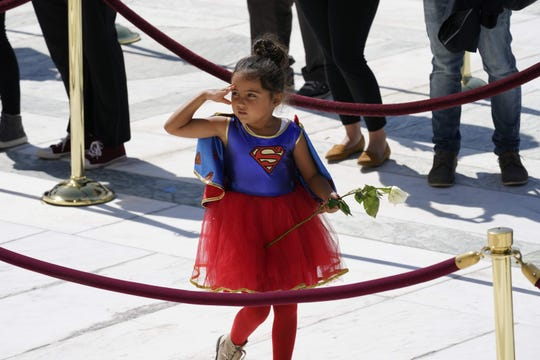 A child in a Supergirl costume pays respects as Justice Ruth Bader Ginsburg lies in repose in front of the U.S. Supreme Court in Washington, D.C., on Sept. 23, 2020.