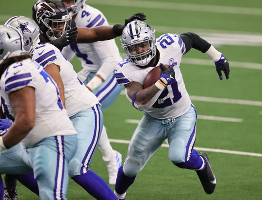 Dallas Cowboys running back Ezekiel Elliott (21) runs with the ball in the second quarter against the Atlanta Falcons at AT&T Stadium.