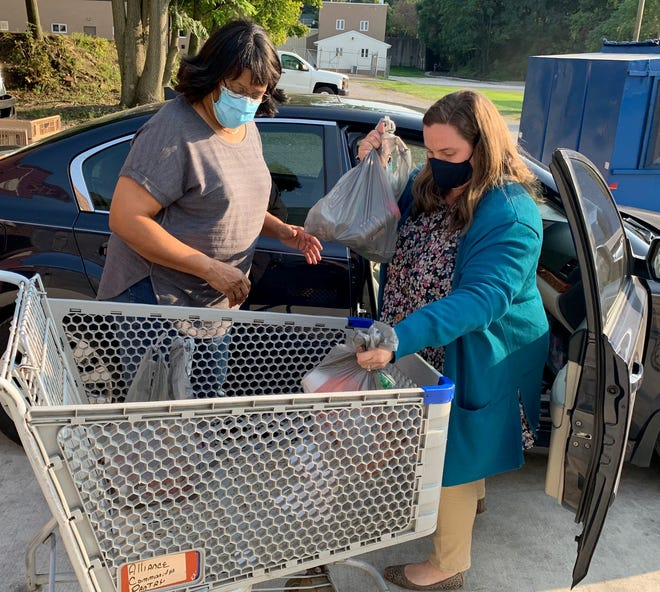 Volunteer Missy Miller, left, and YMCA director Brittany Acuff load food donations from the Alliance Rotary into a shopping cart Thursday at Alliance Community Pantry.