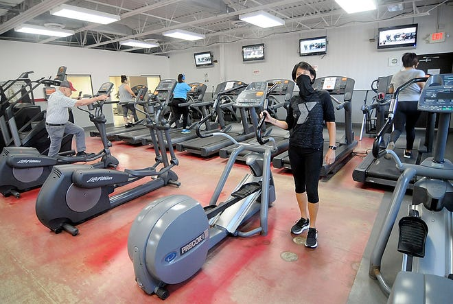 Ashland YMCA CEO Molly Riley poses in the Myers Family Center as members work out on Friday. The YMCA is one of 14 partner agencies  funded by United Way of Ashland County, which kicked off its 2021 campaign Friday.
