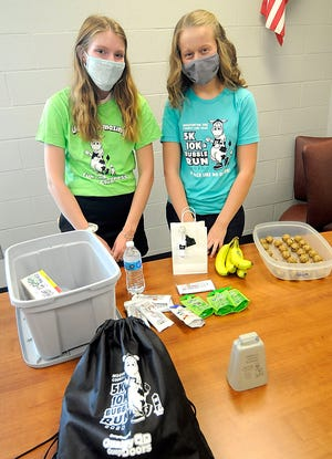 Emma-Jean Stanley and Halle Miller prepare to pack bags for the Moovin on the County Line 5K 10K & Bubble Run. TOM E. PUSKAR/TIMES-GAZETTE.COM