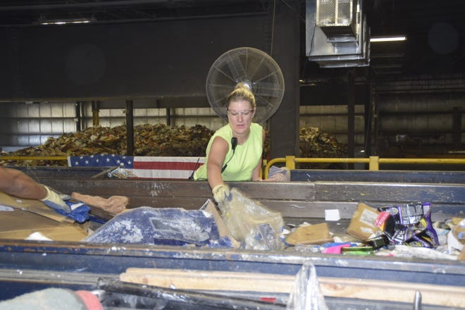 Ashley Bush, of Moorestown, separates items during the recycling process at the county recycling center in Westampton.