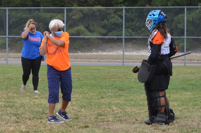 Millville field hockey coach Claudia McCarthy demonstrates a technique with her goaltender.