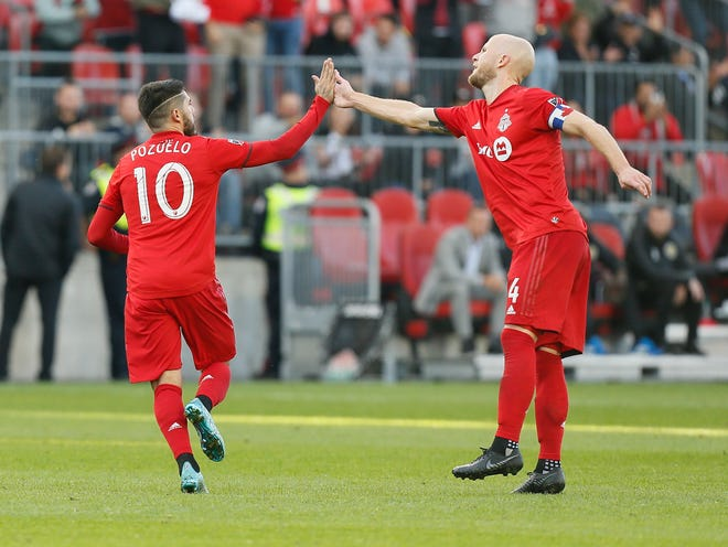 Toronto FC forward Alejandro Pozuelo (10) is congratulated by midfielder Michael Bradley after scoring against the Crew on Oct. 6 at BMO Field. Pozuelo has scored five goals with an MLS-leading eight assists in 13 games this season.[John E. Sokolowski/USA TODAY Sports]