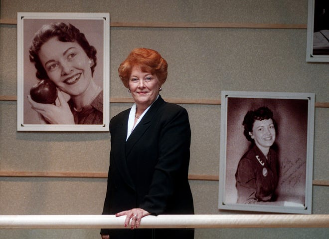 Paula A. Spence, vice chair of HMS Partners, at the Civic Center near her retirement in September 1998. Behind her are photos of her when she was younger.
