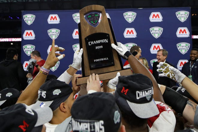 Miami University players hold the champions' trophy after beating Central Michigan in the Mid-American Conference championship game last December in Detroit. The MAC announced on it would reverse its earlier decision and play football this fall.