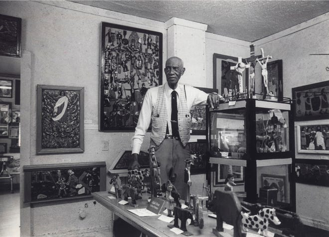 Columbus folk artist and woodcarver Elijah Pierce, seen here in 1982, displays some of his artwork. Pierce, who died in 1984, will be honored with a collection of his work displayed at the Barnes Foundation in Philadelphia. The exhibit will run through Jan. 10.