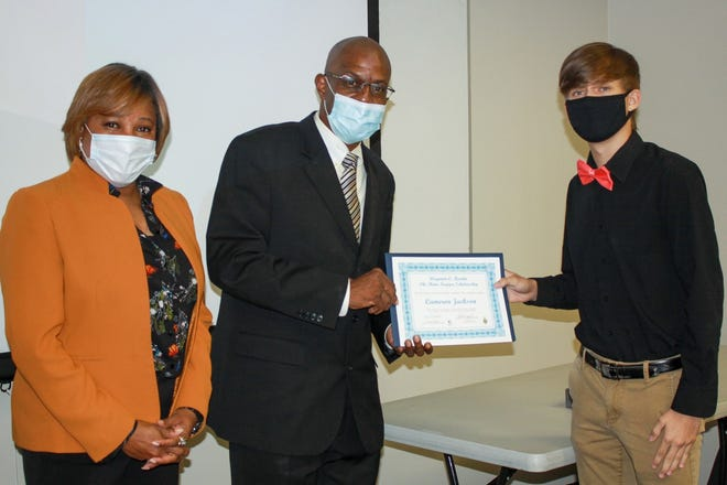 Martin's daughter, Toi Gray, and son, Hosea Martin, present RCC student Cameron Jackson with the scholarship certificate.