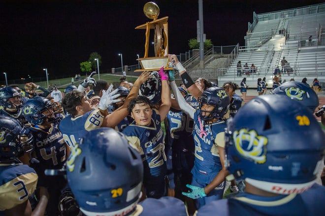 William Chrisman players hoist the Wagon Wheel Trophy for the fifth straight time after defeating rival Truman 21-10 Thursday.