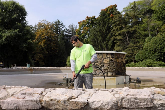 Chance Ebany, with the City of Burlington Parks and Recreation Department, uses a pressure washer to clean Foehlinger Fountain Wednesday in Crapo Park. The cleaning was part of the winterization process for the fountain, other task include cleaning the fountain's filter, flushing pipes and placing a cap atop the fountain.