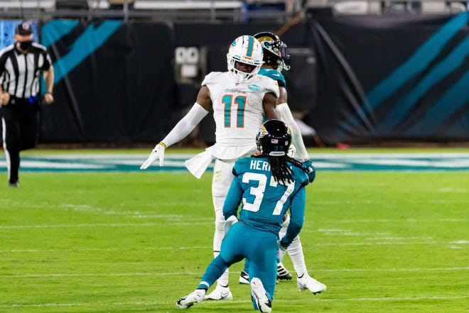 Miami Dolphins wide receiver DeVante Parker (11) stares down Jaguars cornerback Tre Herndon (37) after a first down pass reception on Thursday at TIAA Bank Field.